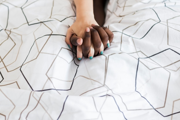 Couple holding hands in bed Free Photo