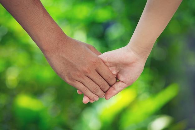 緑の牧草地で手をつないでカップル。 無料写真