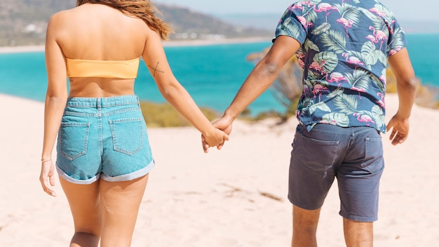 Couple holding hands and looking at sea Free Photo