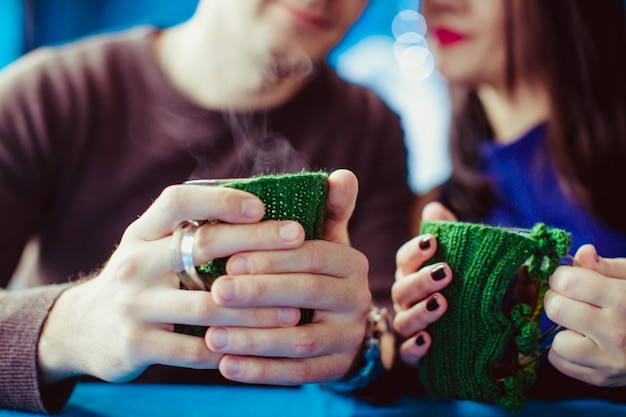 セーターを身に着けているニットのコーヒーカップを持つカップル 無料写真