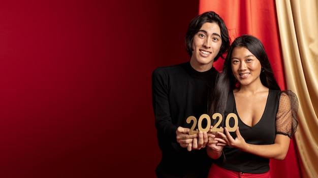 Couple holding new year sign with copy space Free Photo