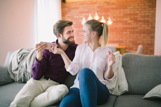 Couple holding smartphone on couch Free Photo