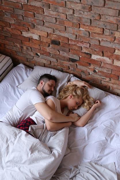 カップルを抱き締めると、ベッドで寝ています。 無料写真