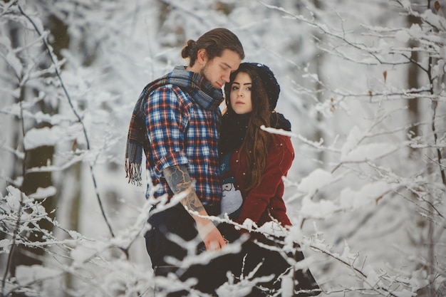 Couple hugging each other in winter forest Premium Photo