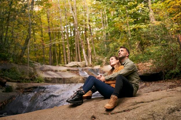Пара обниматься, сидя у реки в лесу Premium Фотографии