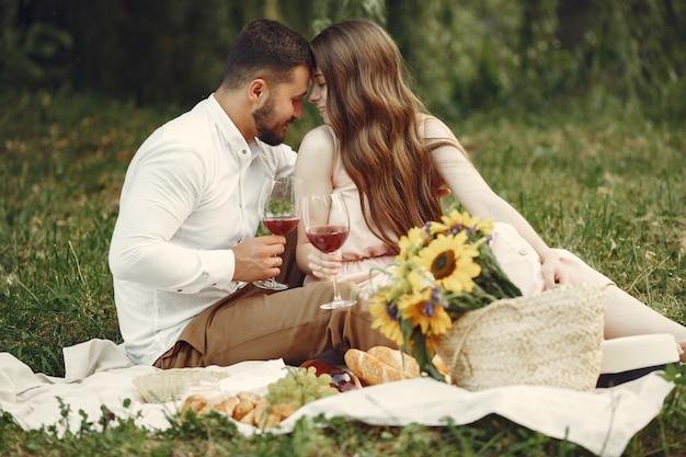 フィールドのカップル。白いドレスを着たブルネット。草の上に座っているペア。 無料写真