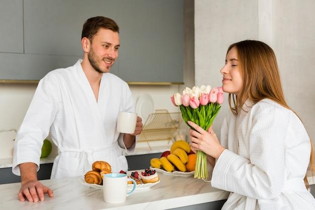チューリップの花束とキッチンでバスローブのカップル 無料写真