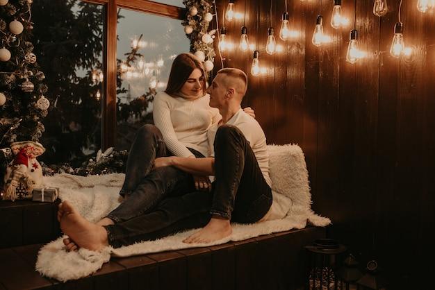 Влюбленная пара парень и девушка обнимаются, целуются возле елки у окна Premium Фотографии