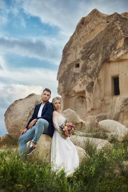 愛のカップルは、自然の中で素晴らしい山で抱擁し、キスします。 Premium写真