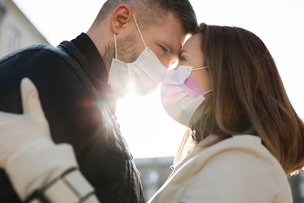 愛、男と女の顔に医療用保護マスクでお互いにキスのカップル。男、パンデミックコロナウイルス、ウイルス保護に対する少女。 covid19 Premium写真