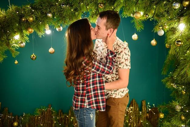 Влюбленная пара возле рождественских украшений молодая пара, целующаяся возле елки. низкий ключ. силуэт. Premium Фотографии