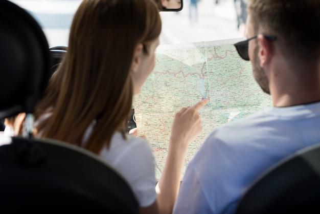 Пара в машине смотрит на карту Бесплатные Фотографии