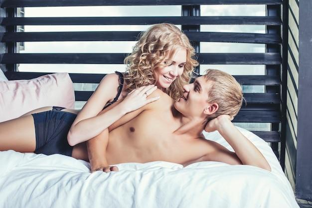 Пара в нижнем белье в спальне на кровати Premium Фотографии