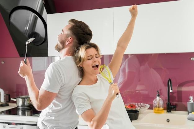Пара в помещении поет на кухне Бесплатные Фотографии
