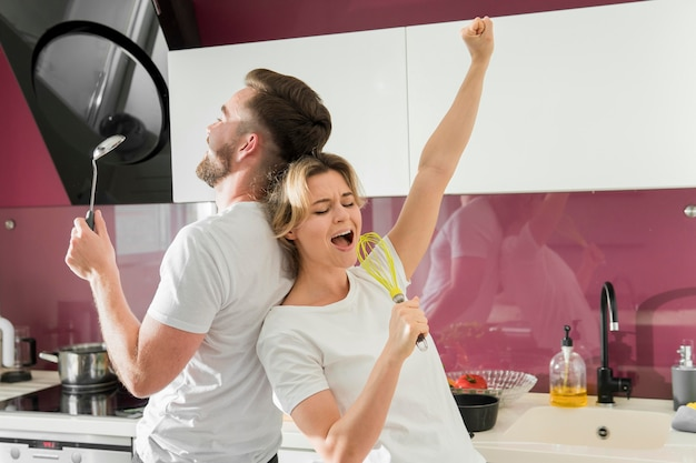 Couple indoors singing in the kitchen Free Photo