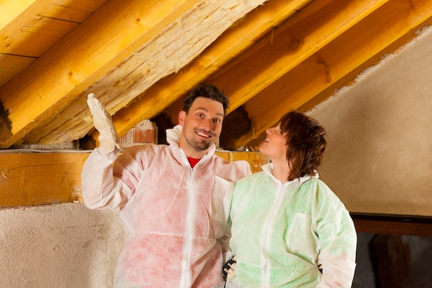 Couple installing thermal insulation to roof Premium Photo