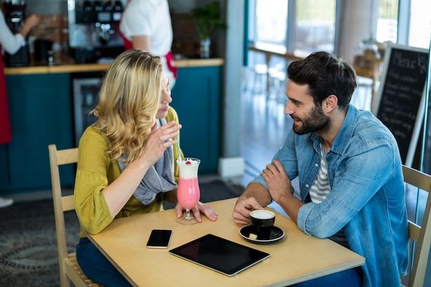 一杯のコーヒーとミルクセーキを持ちながら相互作用するカップル Premium写真