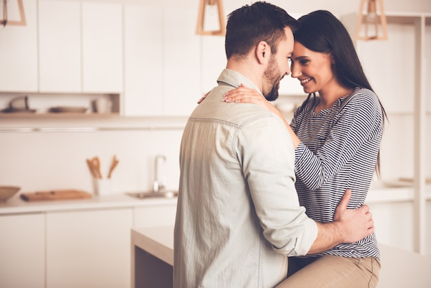 Couple is hugging and smiling while spending time in kitchen Premium Photo