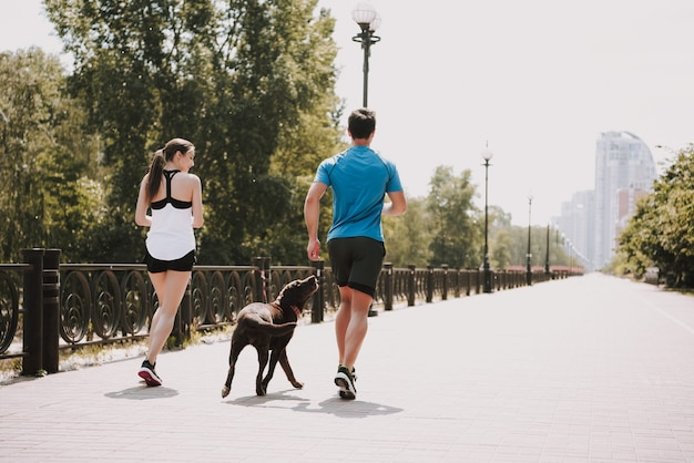 Couple is running with her dog on city path Premium Photo