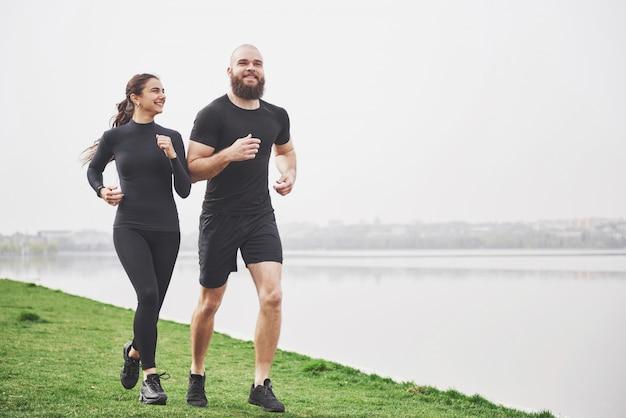 Пара бегом и работает на открытом воздухе в парке возле воды. молодой бородатый мужчина и женщина, осуществляющих вместе утром Бесплатные Фотографии