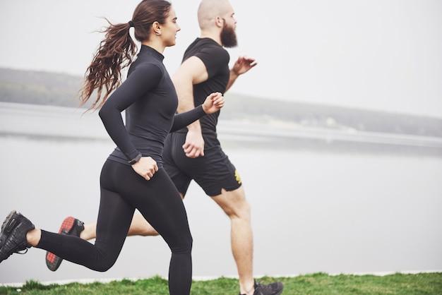 ジョギングや屋外の水の近くの公園で走っているカップル。若いあごひげを生やした男性と女性が朝一緒に運動 無料写真