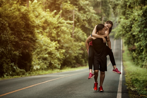 Couple jogging based on a high woman to her boyfriend take her to the finish line. Premium Photo