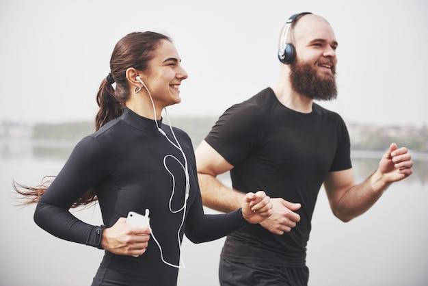 Coppia fare jogging e correre all'aperto nel parco vicino all'acqua. giovane uomo e donna barbuti che si esercitano insieme nella mattina Foto Gratuite