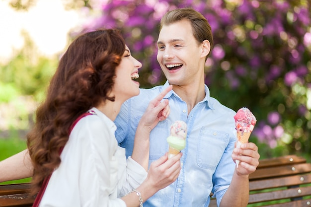 Couple joking and having fun while eating an ice cream Premium Photo