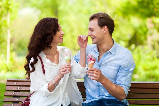 Couple joking and having fun while eating an ice cream Premium Photo