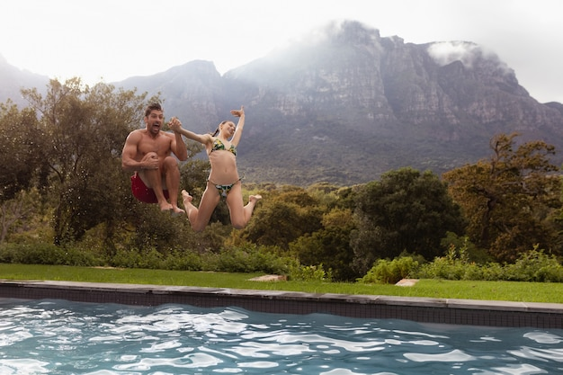 Couple jumping together in the swimming pool at backyard Free Photo