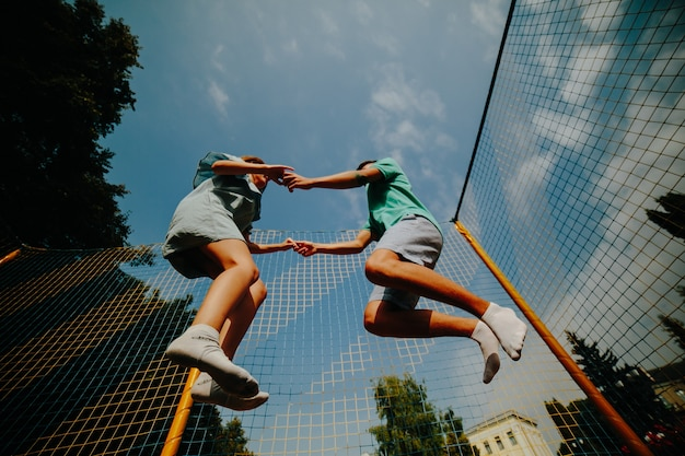 Couple jumping on trampoline Free Photo