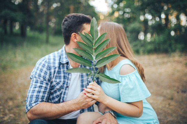 Couple kisses in the forest sitting on a tree branch and closes with a leaf Premium Photo
