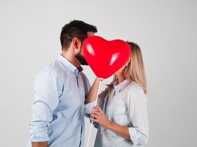 Couple kissing behind balloon for valentines Free Photo