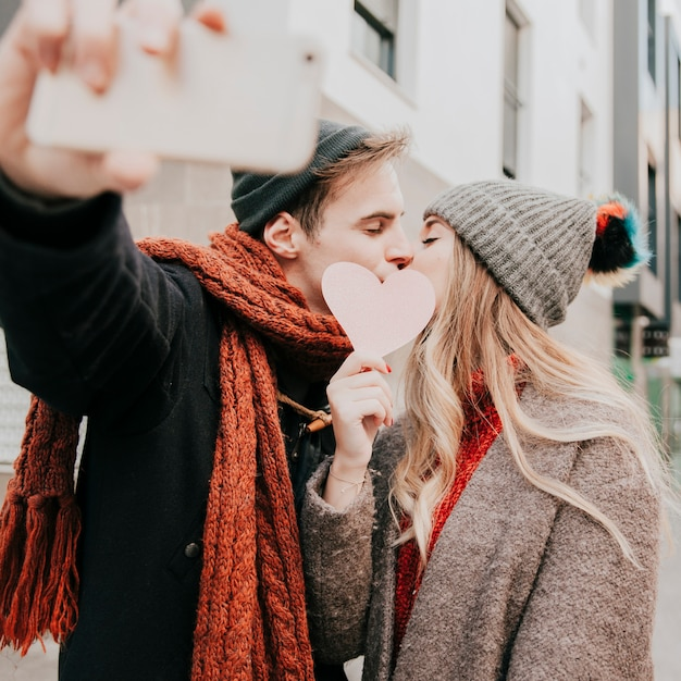 Couple kissing behind heart and taking selfie Free Photo