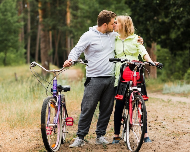 Couple kissing next to bikes on forest road Free Photo