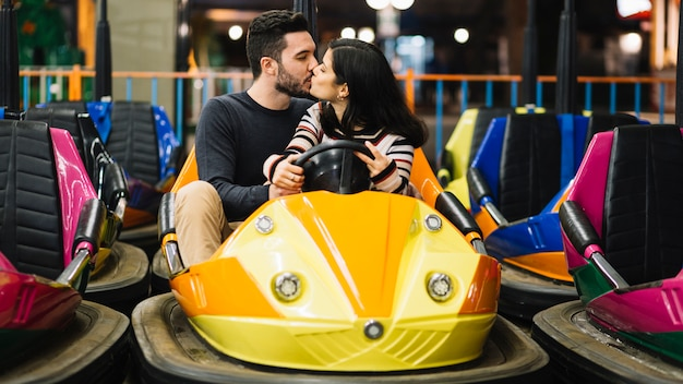 Couple kissing in the bumper cars Free Photo