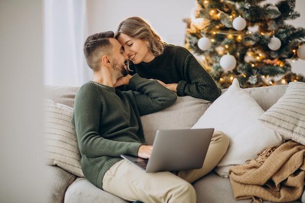 Couple kissing next to christmas tree, using laptop computer Free Photo