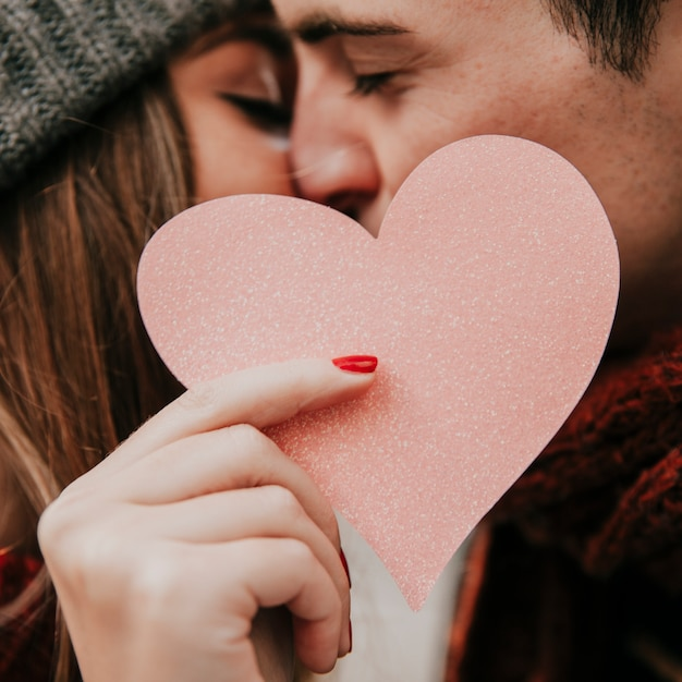Couple kissing and holding heart Free Photo