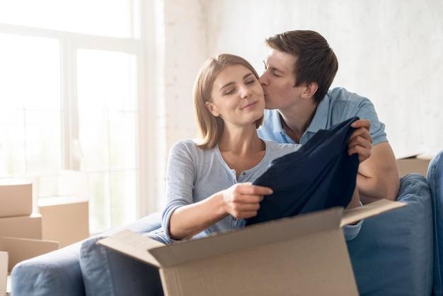 Пара целуется во время упаковки, чтобы съехать Бесплатные Фотографии