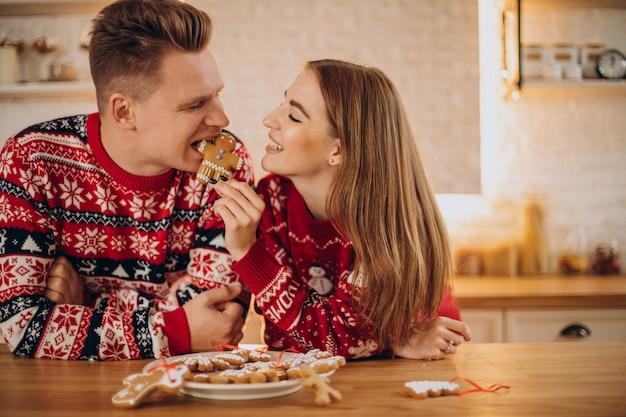 Coppie alla cucina che mangia l'uomo del biscotto di natale Foto Gratuite