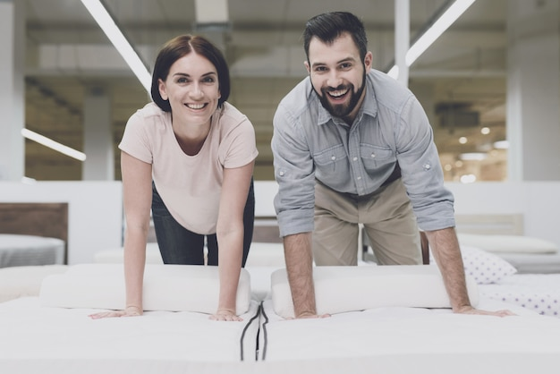 Couple in a large store inspects the mattress before buying. Premium Photo