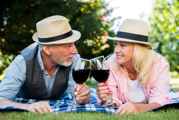 Couple laying on a blanket with wine and hats Free Photo