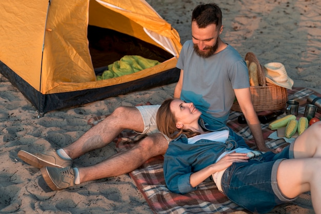Couple laying down near tent Free Photo