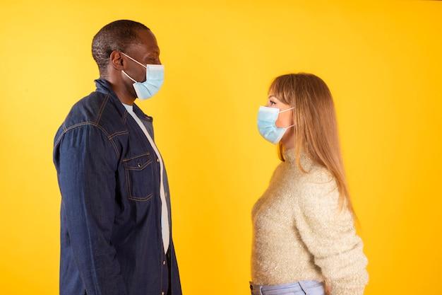 カップルは医療マスク、異人種間のプロフィールビューでお互いを見て、 Premium写真