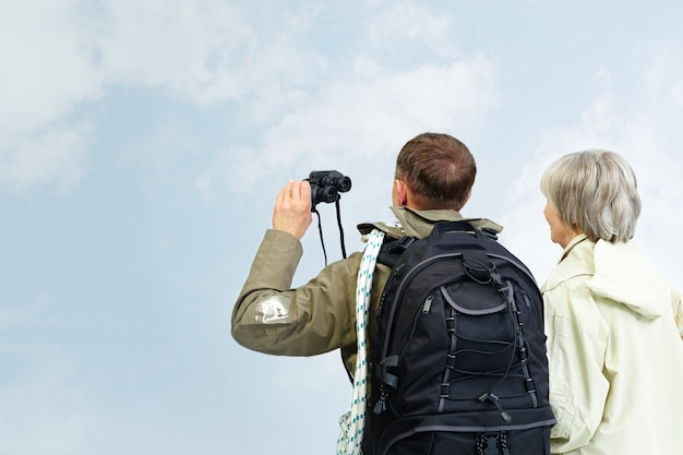 Couple looking at the blue sky with binoculars Free Photo