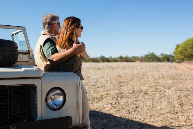 Couple looking away while standing by off road vehicle on field Free Photo