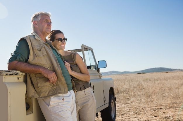 Couple looking away while standing by vehicle on field Free Photo
