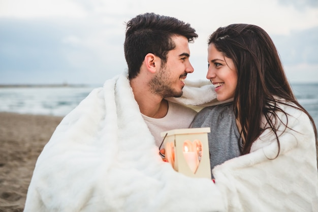 Couple looking at each other in the sand with a candle and a blanket Free Photo