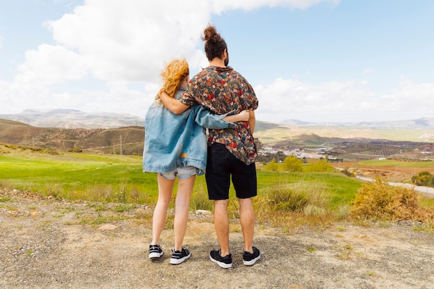 Couple looking into distance from hilltop Free Photo
