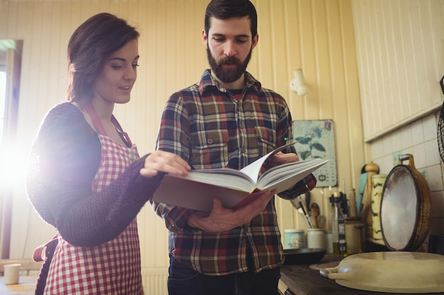 Couple looking at recipe book in kitchen Free Photo